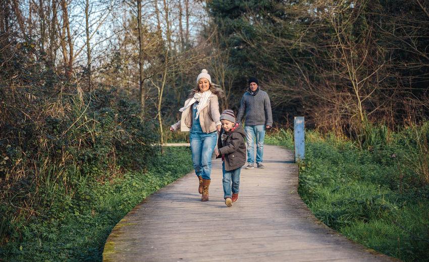 Happy family on boardwalk in forest