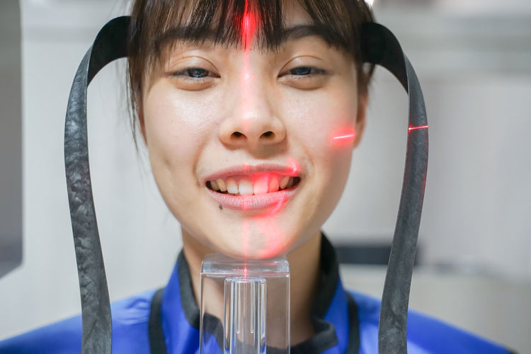 Close-up portrait of smiling woman with medical equipment