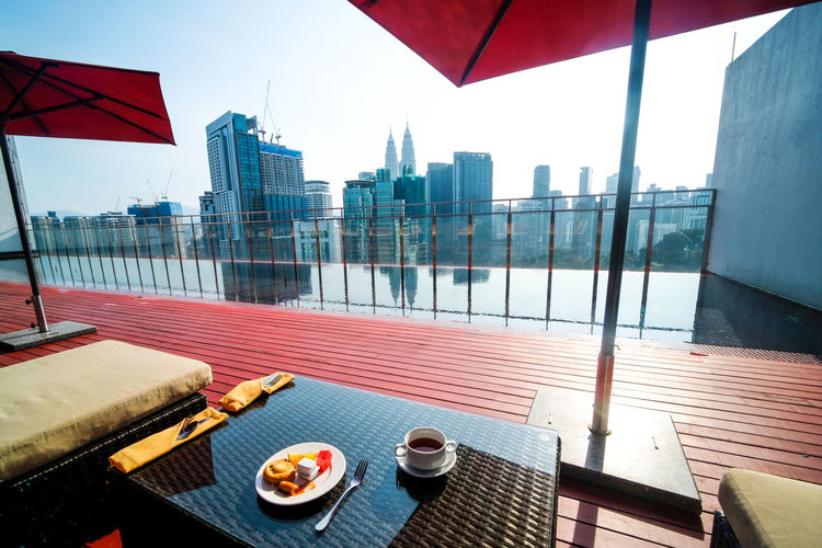 Having breakfast by the roof top pool in the city