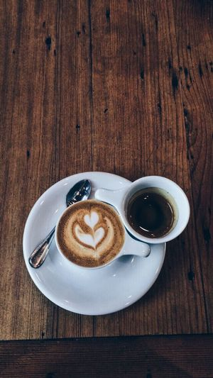 Coffee - Drink Coffee Cup Drink Food And Drink Refreshment Table Saucer Wood - Material Froth Art Frothy Drink Cappuccino Indoors  Freshness High Angle View No People Brown Latte Directly Above Close-up Day