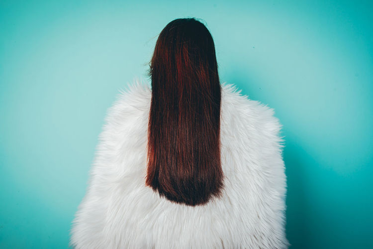 Rear view of woman standing against turquoise background
