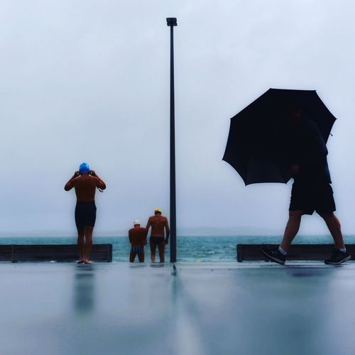 People standing on sea shore against sky