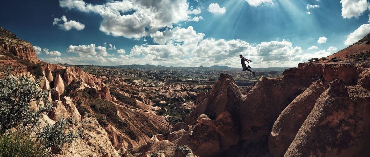 Man jumping from rock formations at cavusin