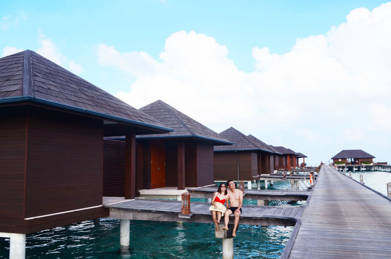 Couple Sitting On Pier By Water Bungalow Against Sky