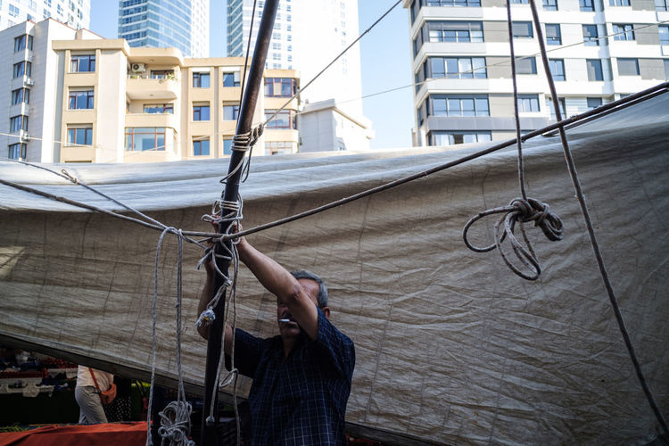 Man holding rope against building in city