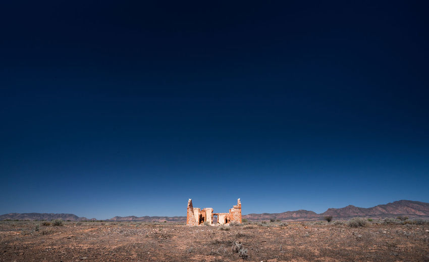 Ruined structure against clear blue sky
