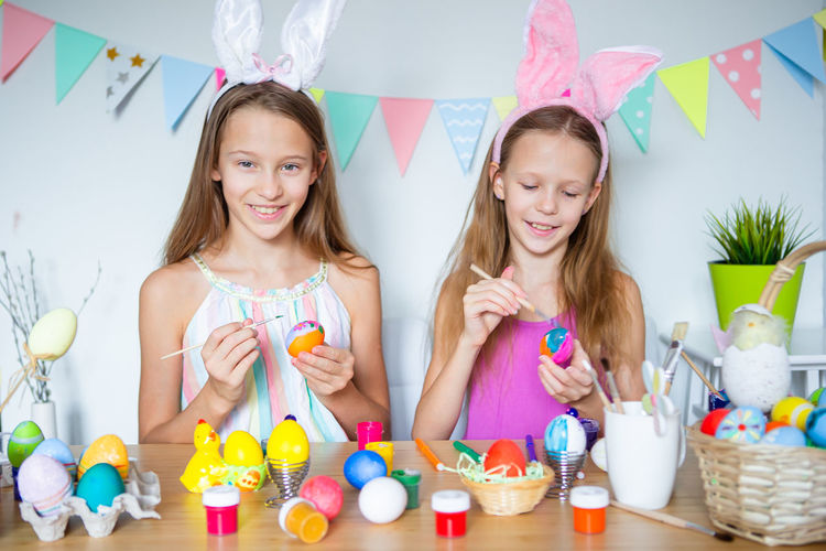 Sibling painting eggs at home