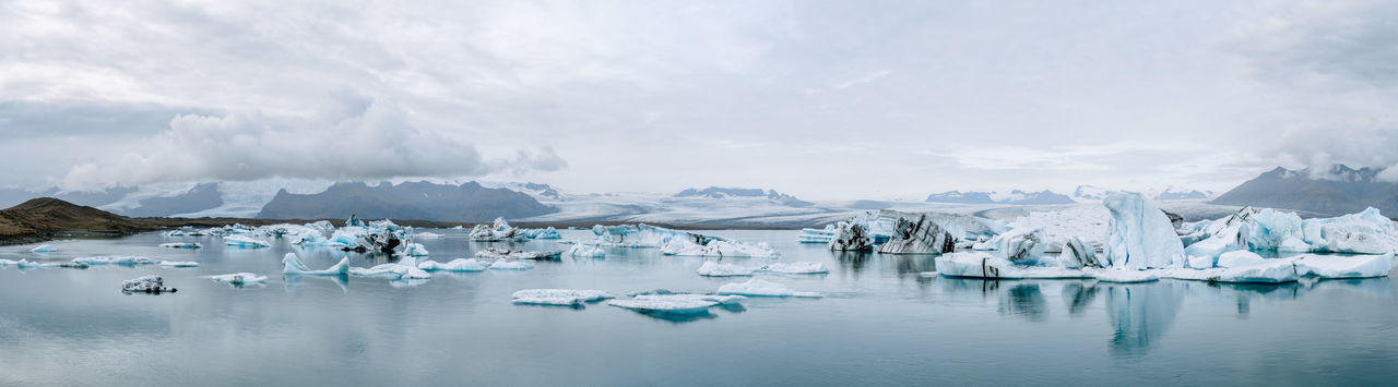 Jökulsárlón glacier lagoon in Iceland panorama during an overcast day Iceland Beauty In Nature Cold Temperature Day Floating On Water Frozen Frozen Water Glacier Ice Iceberg Iceberg - Ice Formation Lake Melting Mountain Nature No People Outdoors Polar Climate Reflection Scenics Sky Snow Water Winter