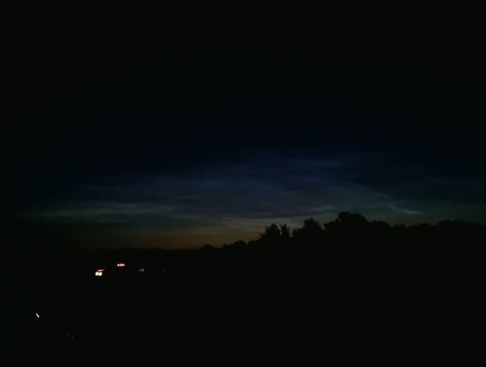 Low angle view of silhouette landscape against sky at night