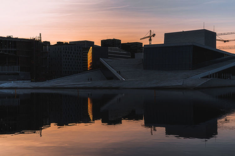 Silhouette Buildings By Lake Against Sky During Sunset In City