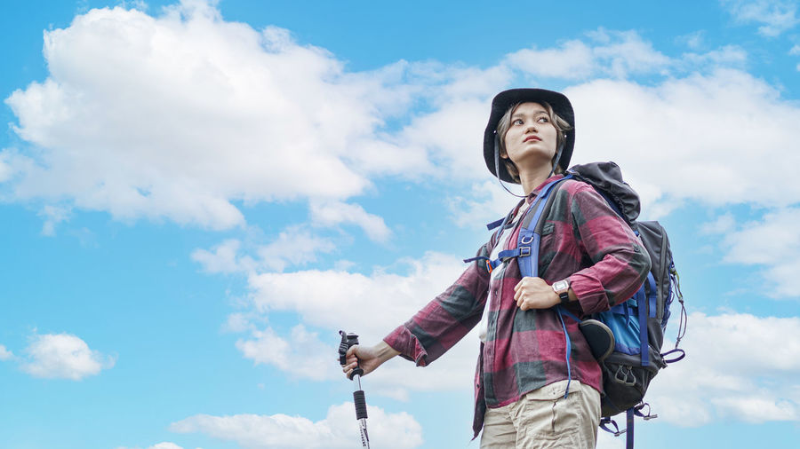 Low angle view of woman looking away against sky