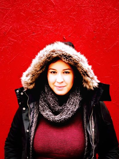 Portrait Of Smiling Woman In Warm Clothes Against Red Background