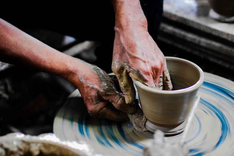 Cropped hands of man making pot in workshop