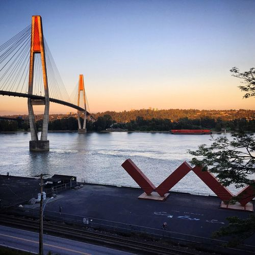 Skytrain Bridge glowing during the Golden Hour . WOW Vancouver Biennale Sculpture New Westminster Westminster Pier Park Fraser River Surrey