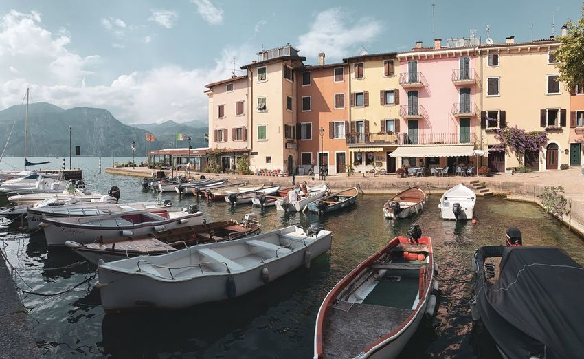 Boats moored at harbor by buildings in city