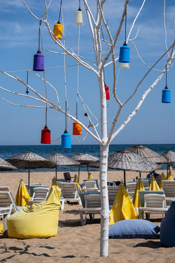 Lounge chairs on beach against sky