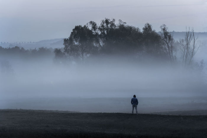 Dramatic nature landscape with a man standing, alone in the cold, on a meadow, contemplating the dense mist, near Schwabisch Hall, Germany. Autumn Darkness Low Light Cold Season Creepy Dramatic Landscape Environment Field Fog Foggy Landscape Hazy  Misty Landscape Misty Morning Mystery Nature One Person Outdoors Scenics - Nature Shadow Spooky Tranquil Scene Tranquility
