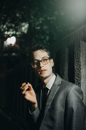 Young man smoking a cigarette Lifestyle Smoking Business Cigarette  Eyeglasses  Focus On Foreground Formalwear Front View Glasses Holding Lifestyles Looking Men Night One Person Outdoors Portrait Real People Suit Waist Up Well-dressed Young Adult Young Men