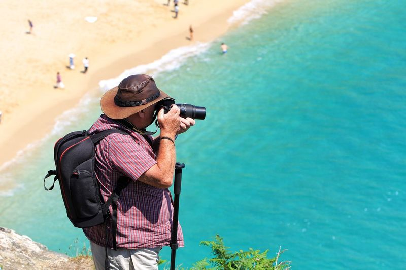 View of man photographing beach from cliff