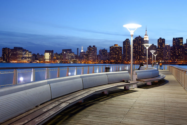 Pier over river against illuminated buildings in city