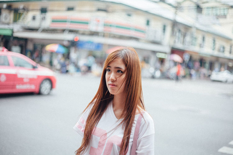 Portrait of young woman on street in city
