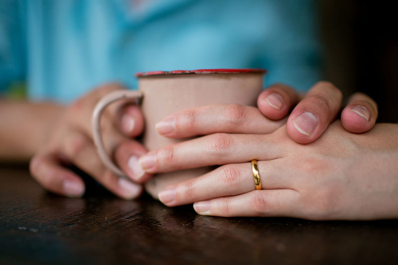 Cropped Image Of Couple Holding Coffee Cup At Table