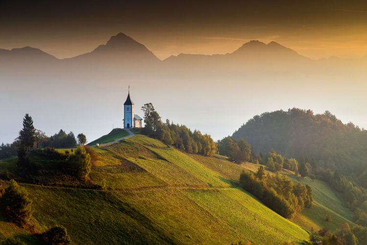 Scenic view of church on landscape against mountain range