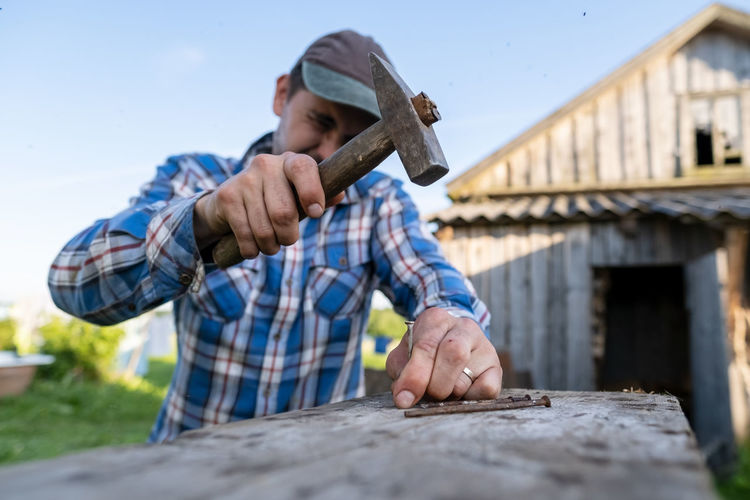 Carpenter using hammer outdoors