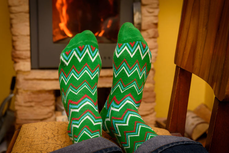 Warming up feets. Warm socks near open fire place at room. Human Body Part One Person Sock Green Socks Heating Warm Socks Wool Socks Fire Place Open Fire Place Room Interior Design Cold Legs Cold Feet