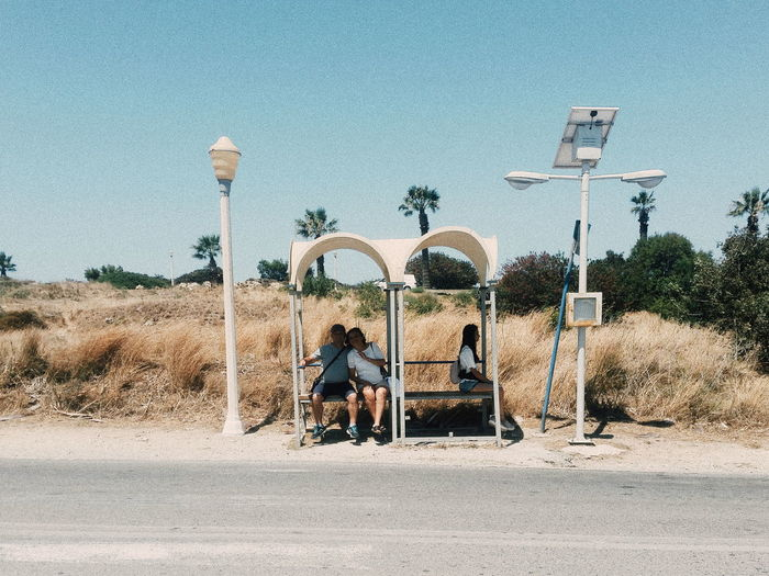 People Sitting At Bus Stop Against Clear Blue Sky