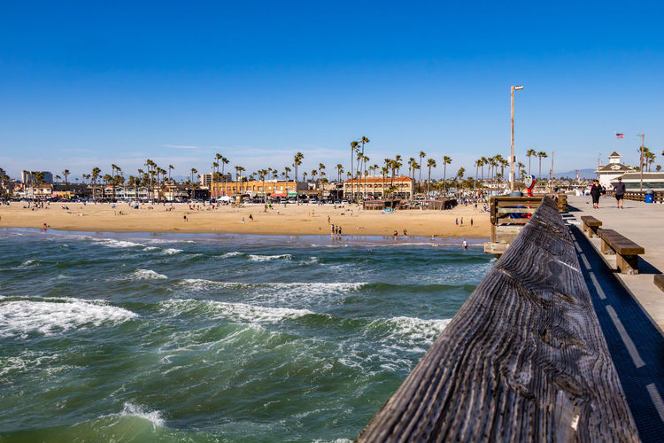 Outdoors Crowd Transportation Pier Clear Sky Wave City Building Exterior Motion Day Incidental People Built Structure Nature Blue Architecture Land Beach Sky Sea Water Sunlight Scenics - Nature Newport Beach