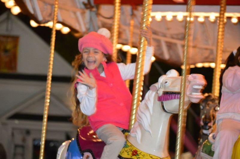 Cheerful Girl Enjoying While Sitting On Carousel Horse
