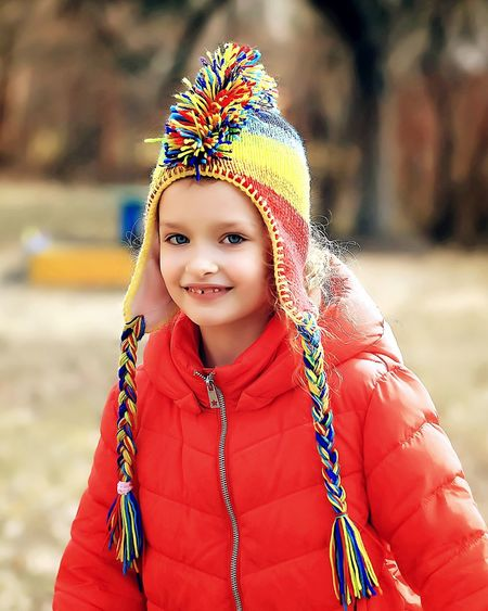 Portrait of smiling girl wearing warm clothing at park