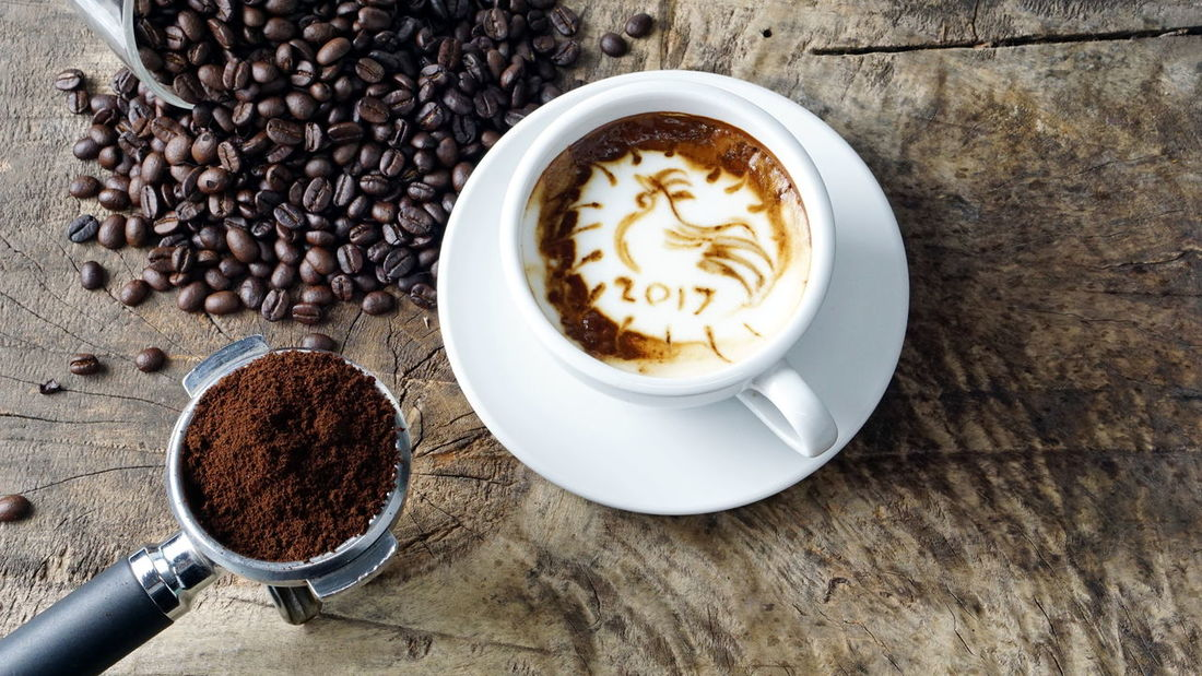 Rooster Coffee. A cup of latte, cappuccino or espresso coffee with milk put on a wood table with dark roasted coffee beans Aroma Bakery Beans Boiler Cafe Cappuccino Coffee Cookies Cream Cup Drink Espresso Fresh Headshot Latte Make Mashed Milk Morning Plate Pressure Roasted Robust Stream Table