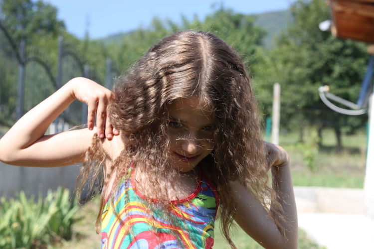 Close-up portrait of girl standing with hands on shoulders against trees