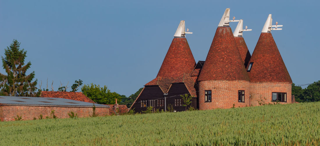 Oast house,Garden of England, Kent, England. Architecture Built Structure Building Exterior Building Sky Grass Plant House Field No People Nature Day Clear Sky Landscape Land Residential District Tree Growth Roof Rural Scene Outdoors Oast House Hops Travel Destinations Tourism Getty Images History Vivid International Village Tranquil Scene Wheat Field Church Tower