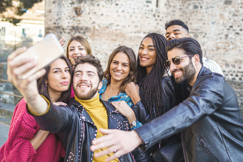 Young man taking selfie with cheerful friends in city