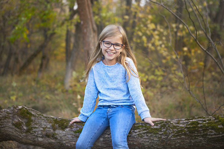 Smiling young woman standing against trees in forest