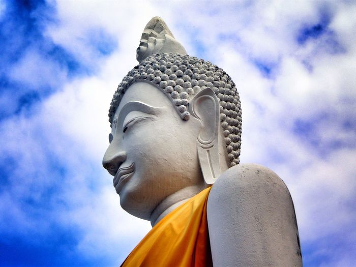 Low angle view of buddha statue against cloudy sky