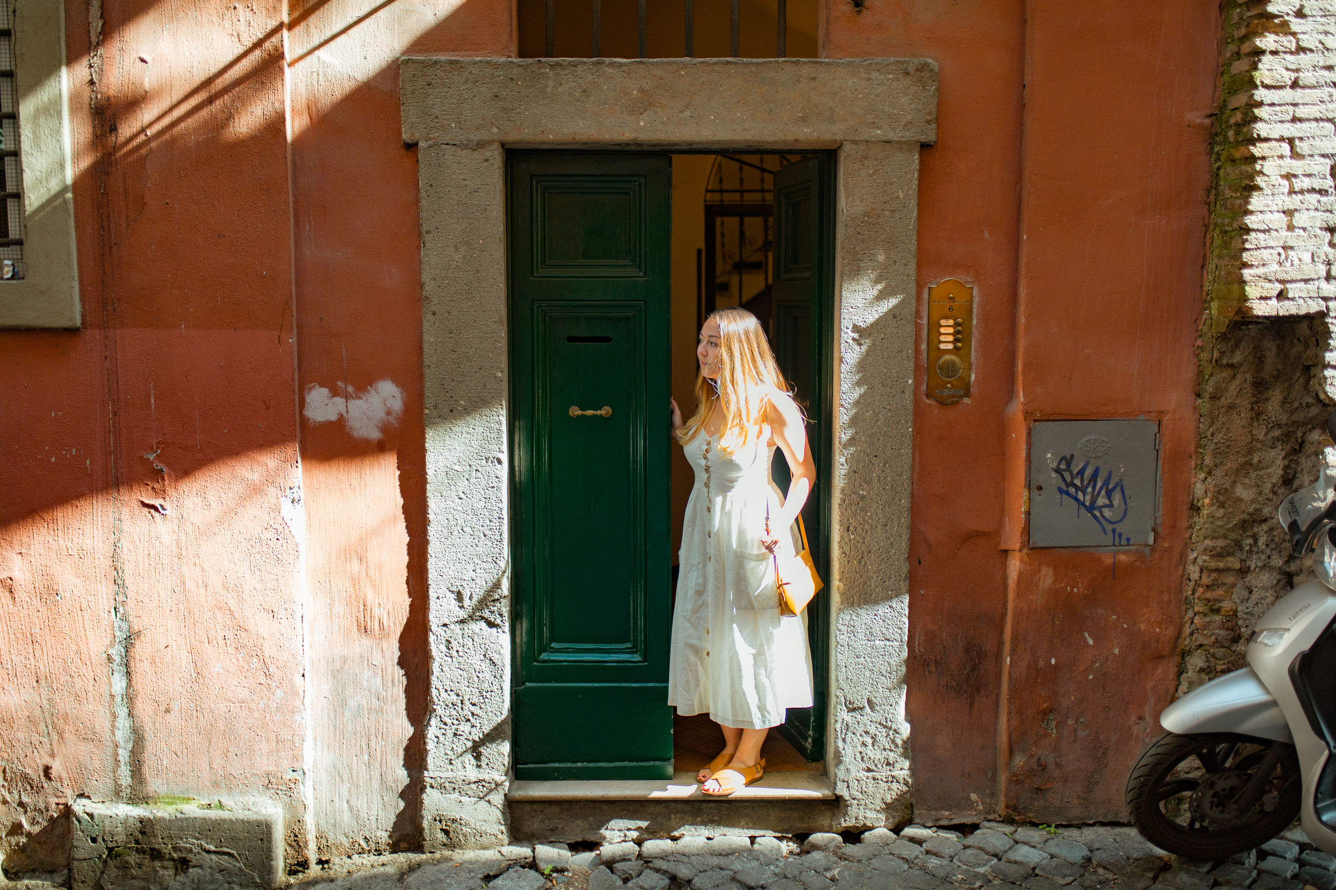 architecture, building exterior, built structure, building, day, entrance, real people, door, full length, women, one person, adult, clothing, house, religion, outdoors, wall - building feature, sunlight, traditional clothing, obscured face