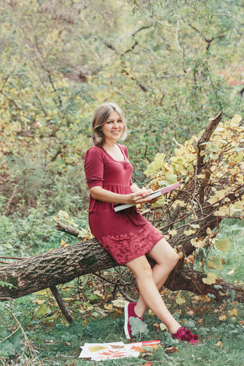 Portrait of smiling woman sitting on tree trunk in forest