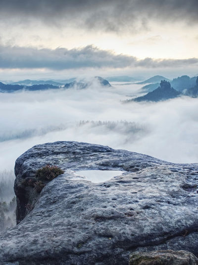 Low clouds float between mountains. dense fog lies in mountainous valley among greenery