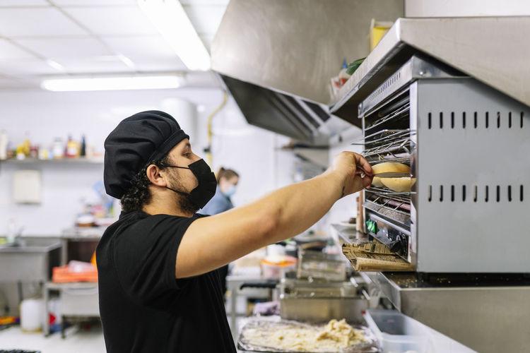 Side view of woman preparing food