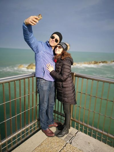 Smiling couple taking selfie while standing by railing against sky