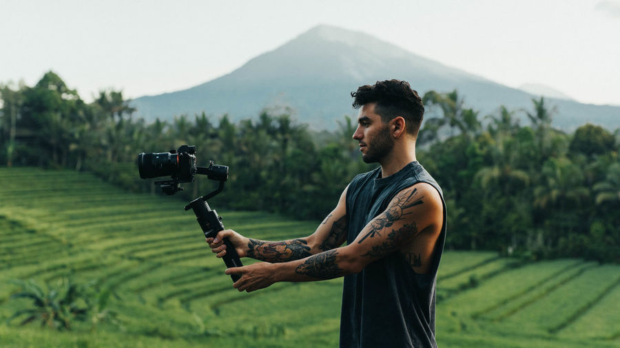 Side view of young man photographing on field