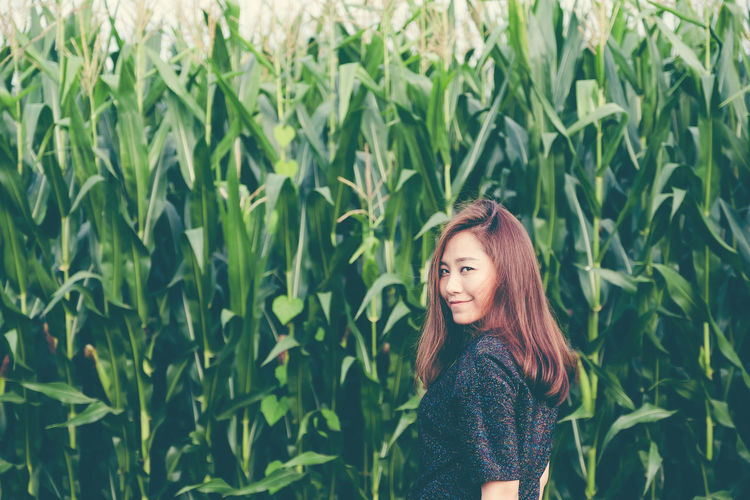 Portrait of smiling woman standing against crops in farm