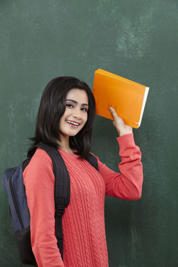 Portrait of happy female student holding book while standing by blackboard