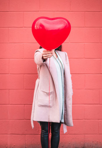 Woman holding heart shape balloon against wall