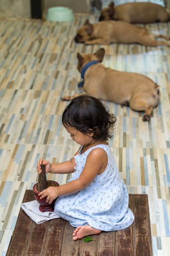 High angle view of girl playing with mortar and pestle at home