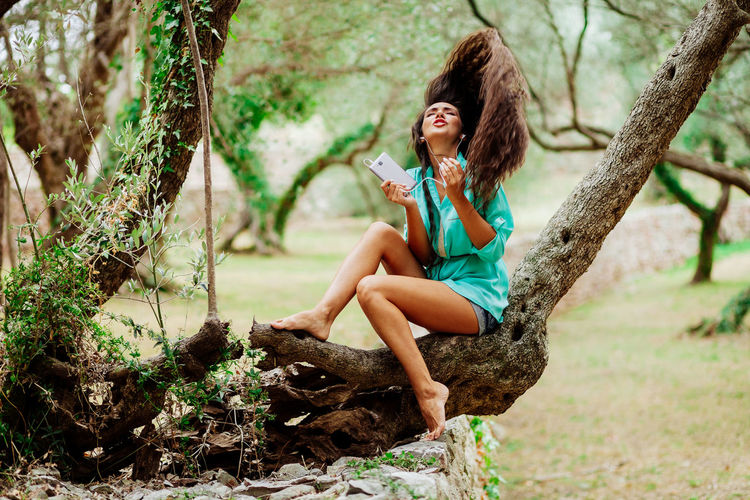 Woman tossing hair while listening music on headphones in forest